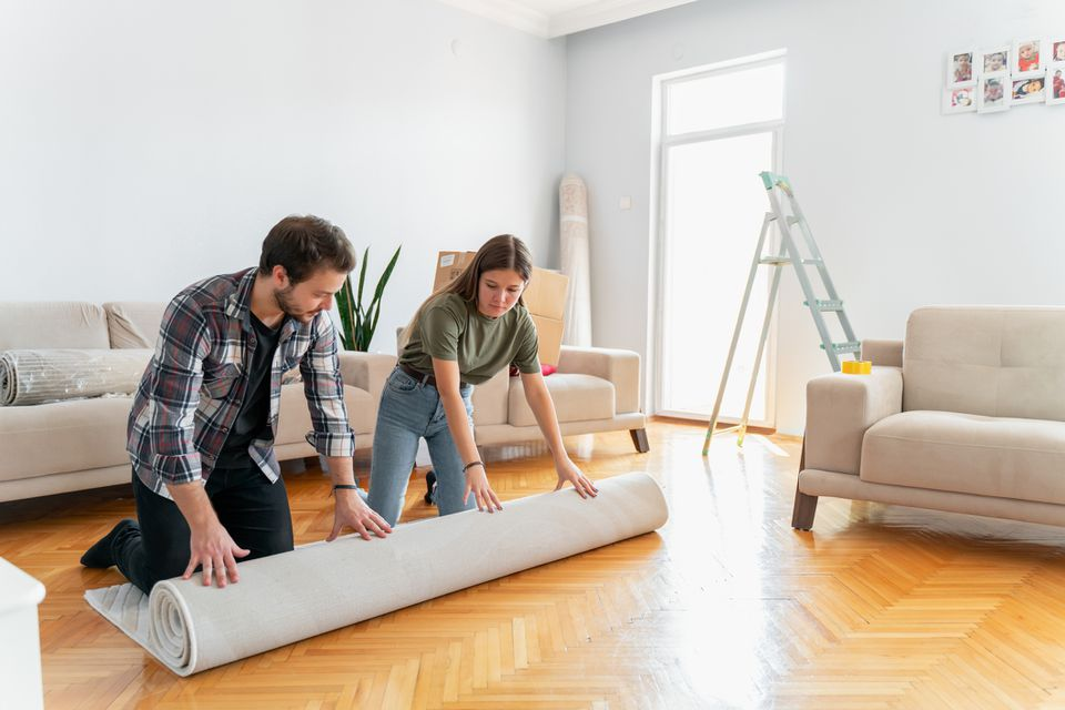 Couple unrolling a rug