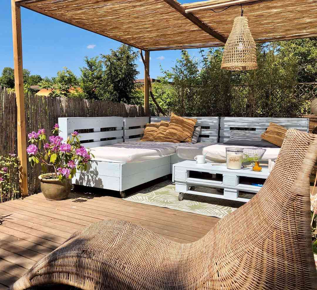 An outdoor living room with wood pallet furniture and a woven pendant light