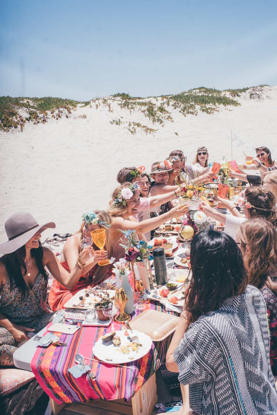 Group of friends at a long dinner table on the beach