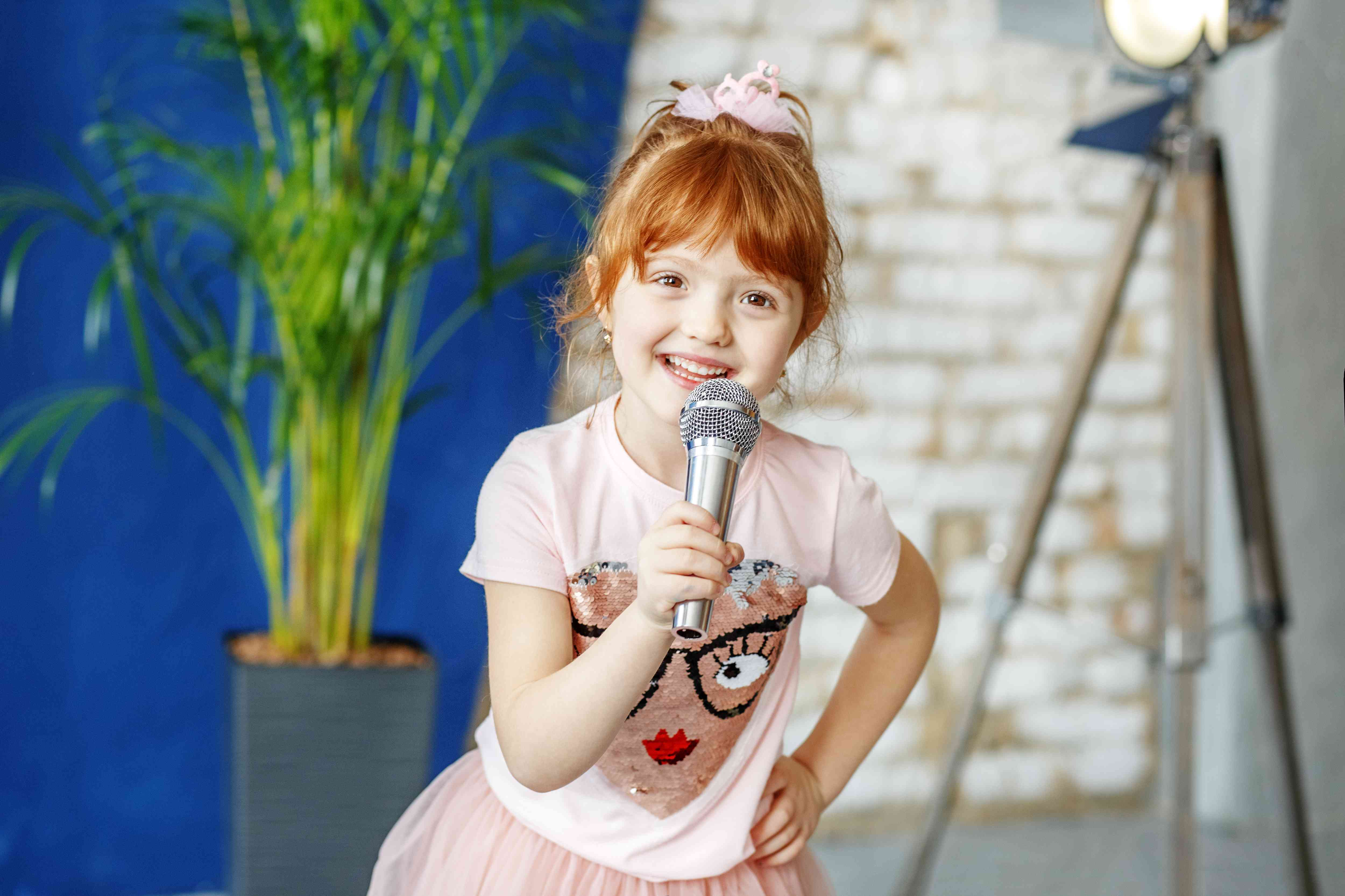 Smiling child sings a song into the microphone. The concept is c
