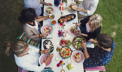 Friends sitting at a long table sharing a meal outside