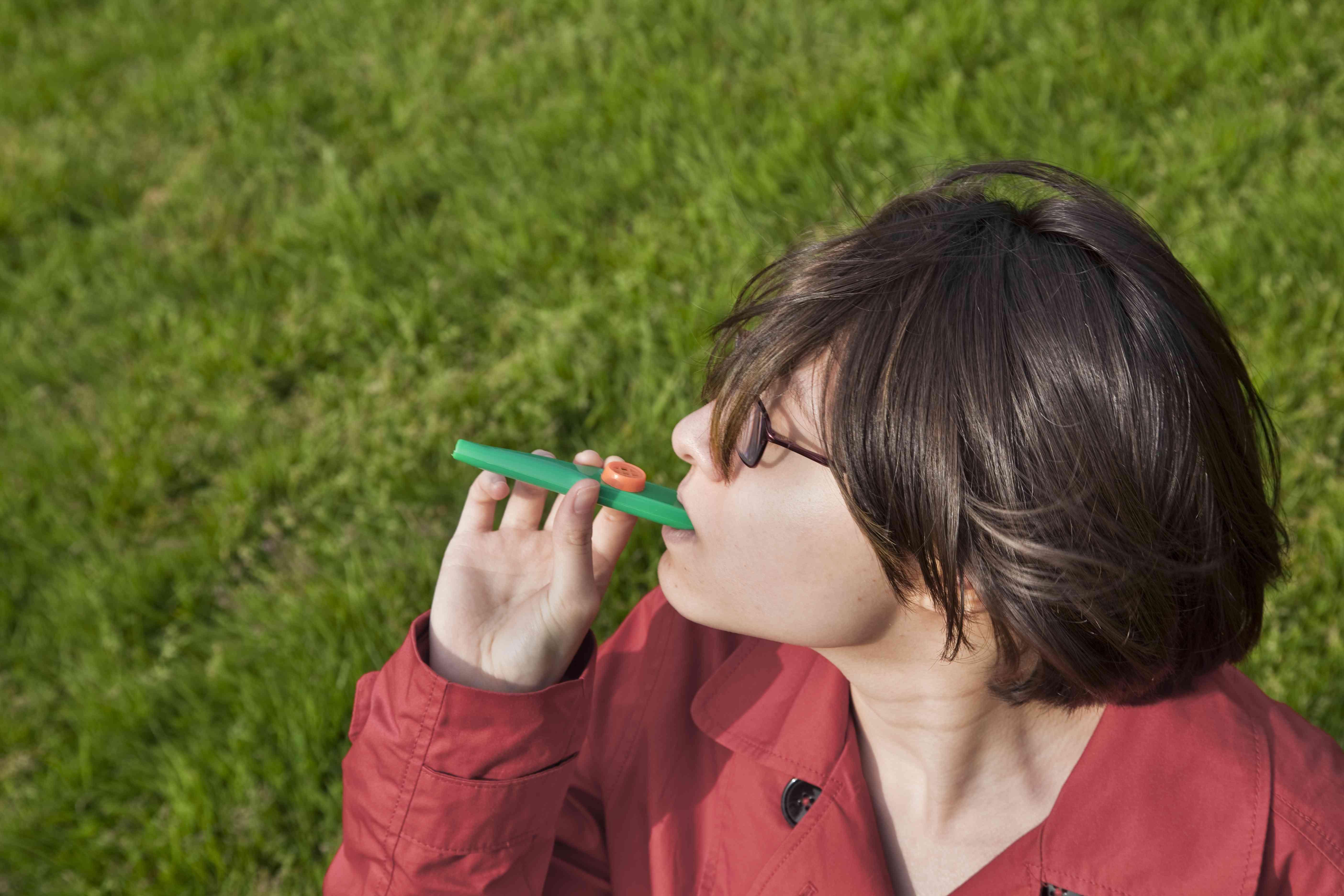 Eurasian teenage girl playing a kazoo.