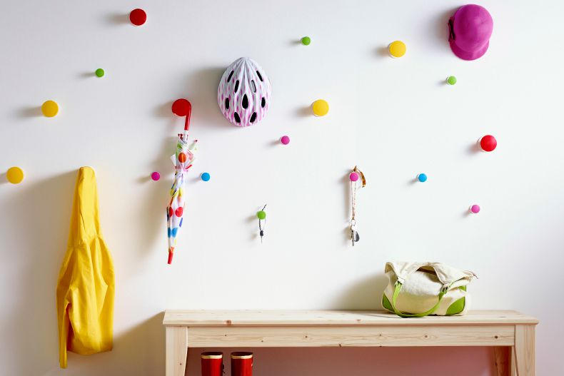 Ikea LOSJÖN knobs scattered on a wall for hanging storage