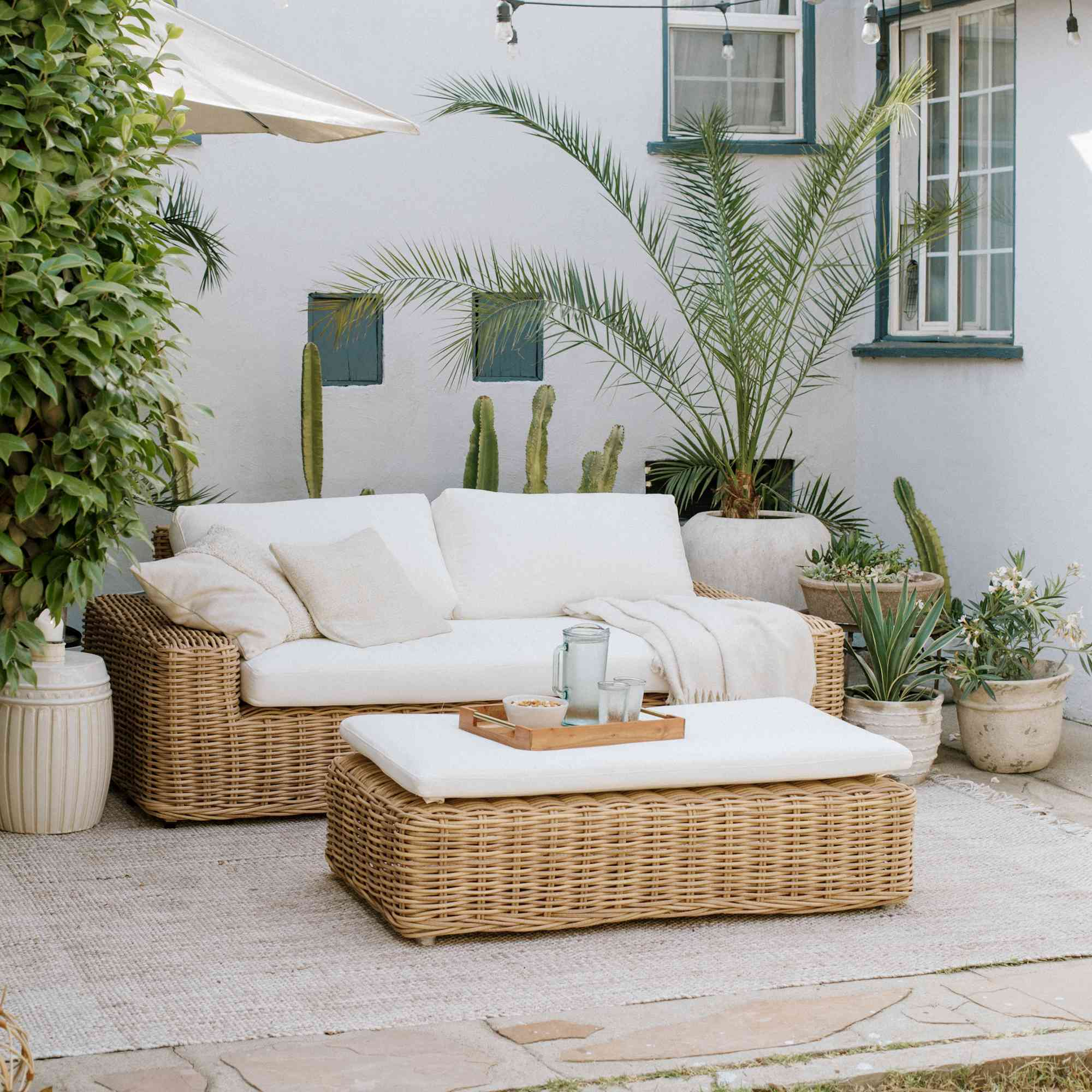 rattan furniture with white cushions adorn this lovely patio, which also features plants and string lights