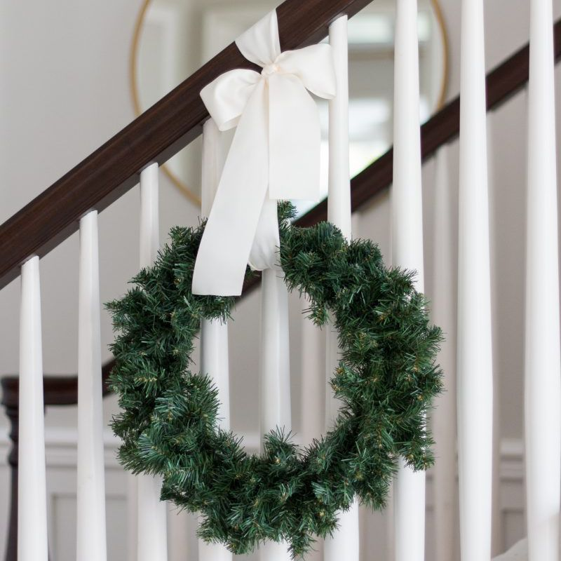 hang wreathes on the banister staircase with a wreath