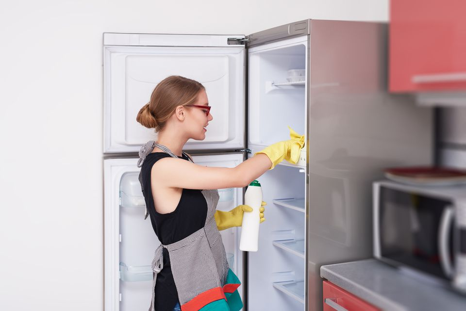 Woman cleaning out her refrigerator before moving it