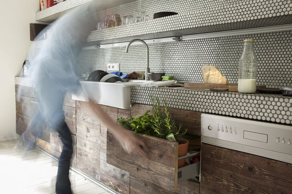 Blurred man opening wooden drawer with herbs with tile backsplash