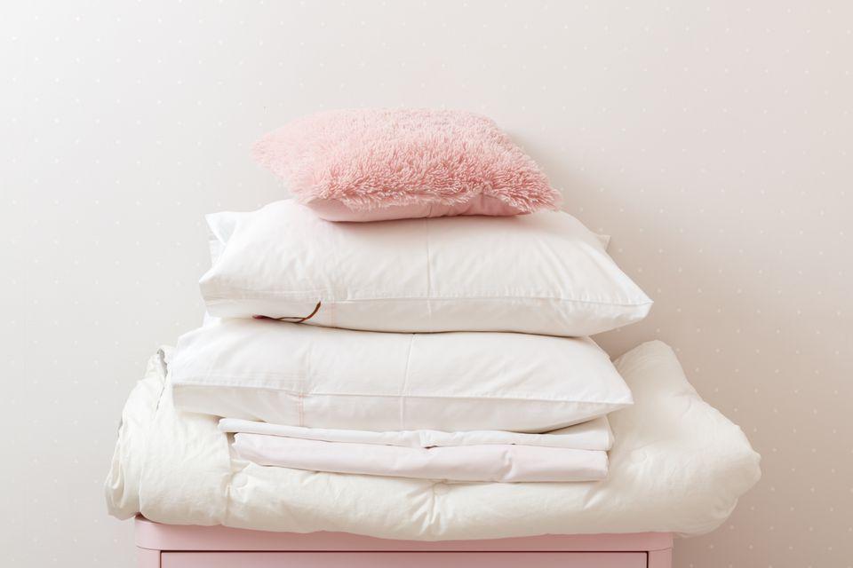 Una pila de ropa de cama limpia y planchada y una toalla descansa sobre la cómoda.
