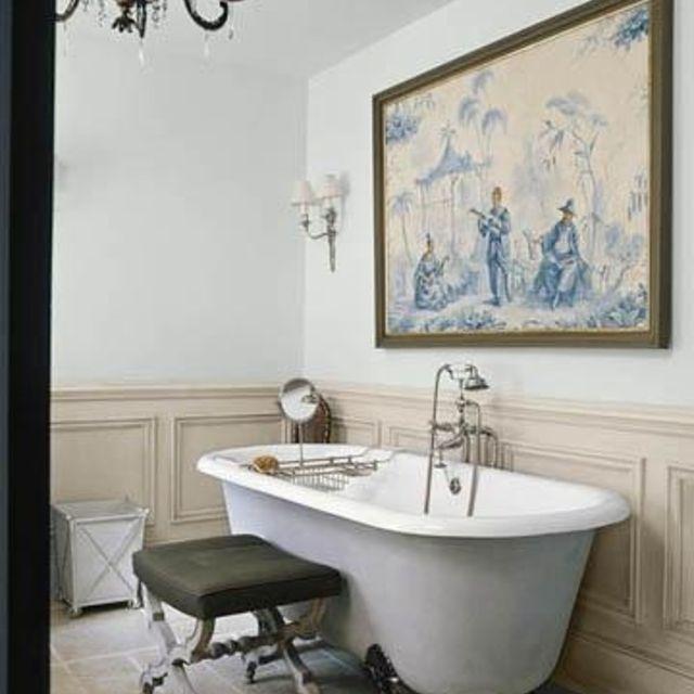 baño con arte vintage y una bañera con patas