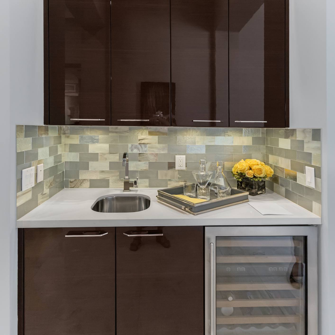 Modern home bar with wine fridge and brown cabinets