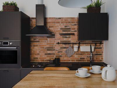 Black stainless steel appliances in brick walled kitchen