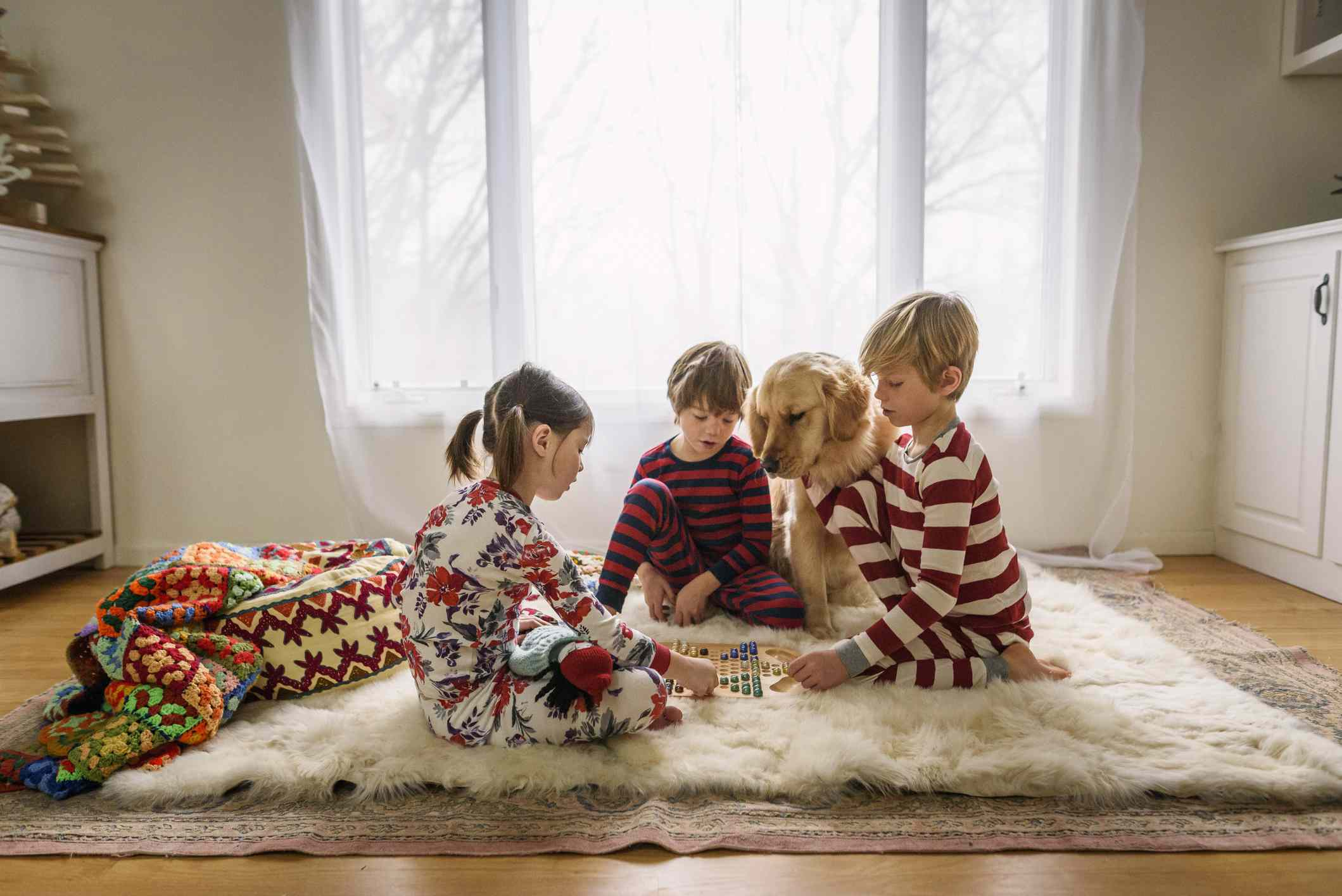 Kid's playing a board game with dog