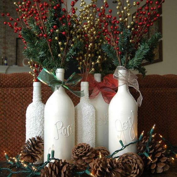 White bottles with festive yellow and red branches surrounded by pine cones and lights.