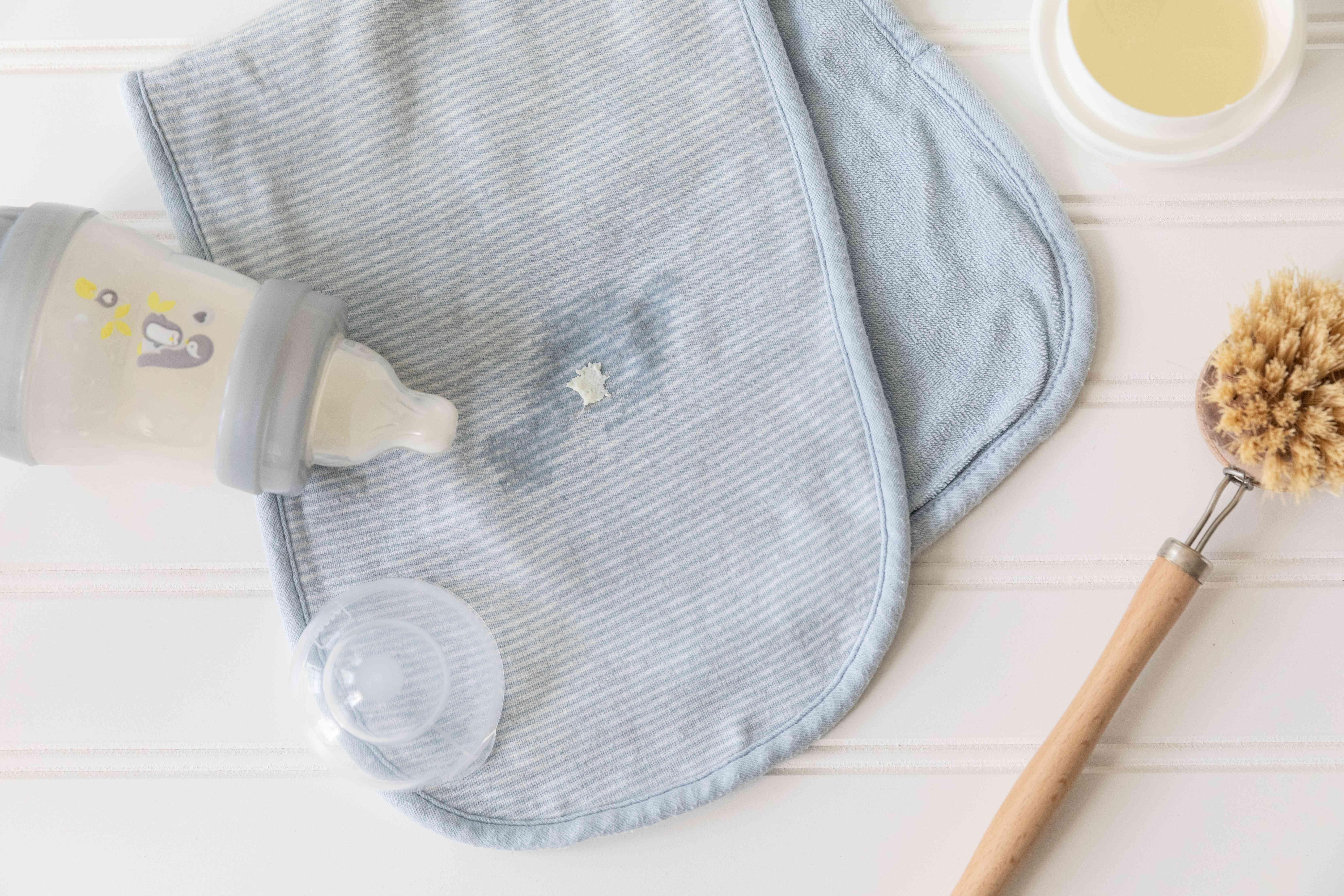 Baby bottle with protein formula spilled on blue bib next to soft-bristled brush