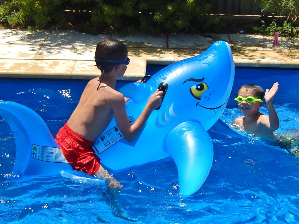 A boy rides a shark pool float and another boy high fives it