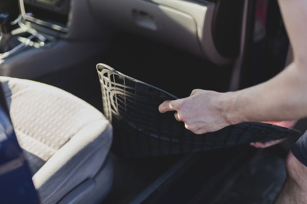 Someone putting car floor mats into a car