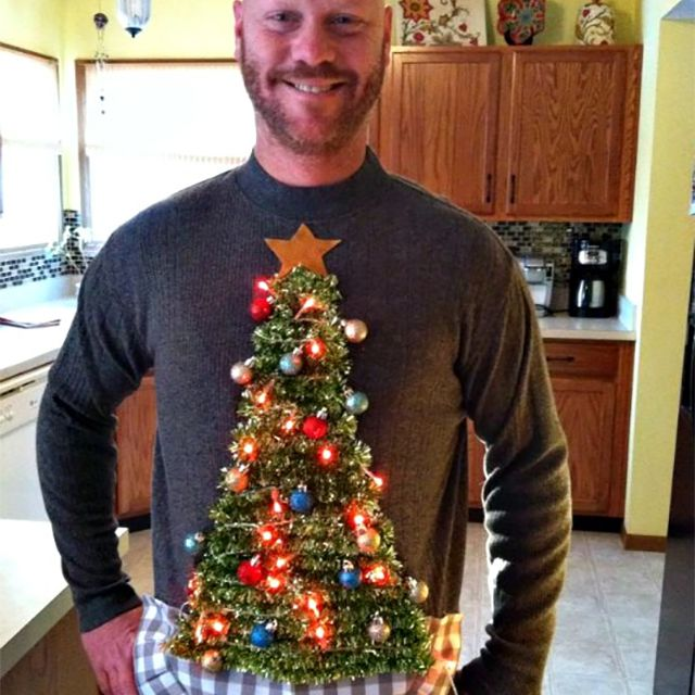 A man wearing a sweater with a Christmas tree on it