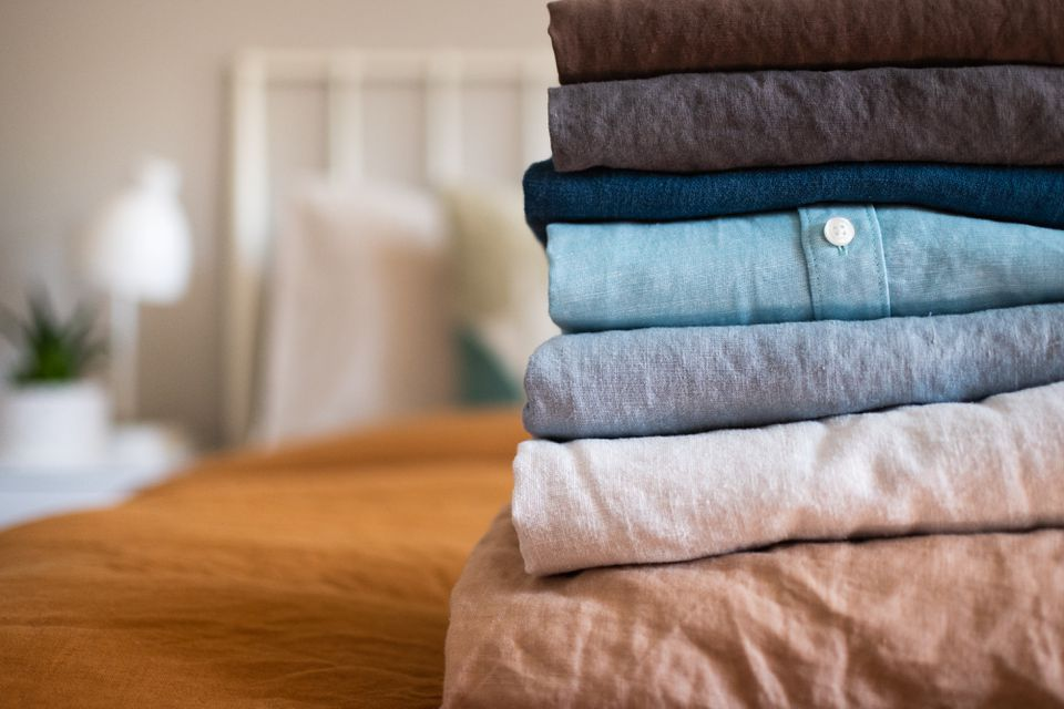 Linen shirts folded and stacked on bed with yellow cover