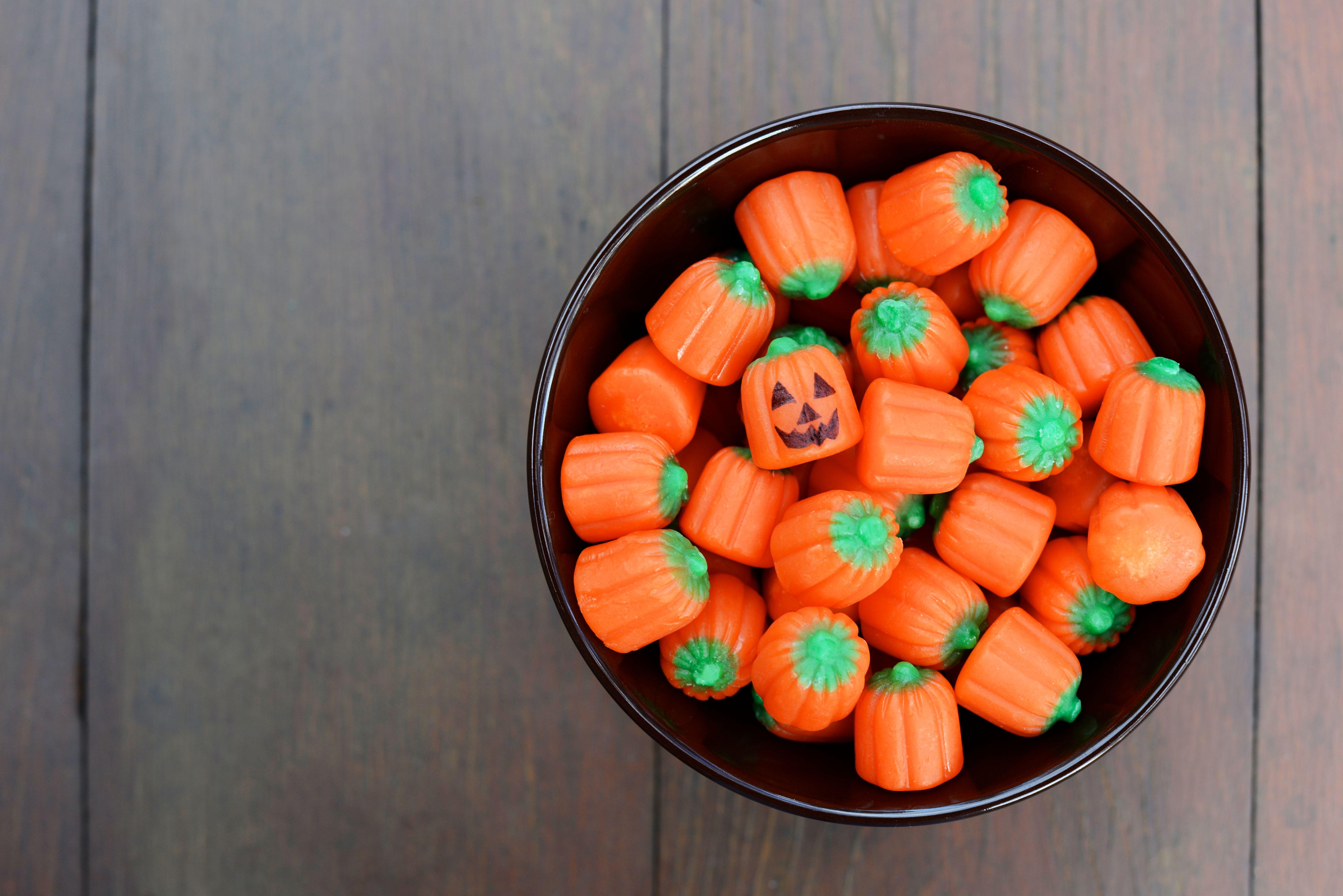 Bowl of pumpkin shaped Halloween candy.