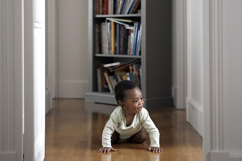 Baby crawling through hallway looking through door