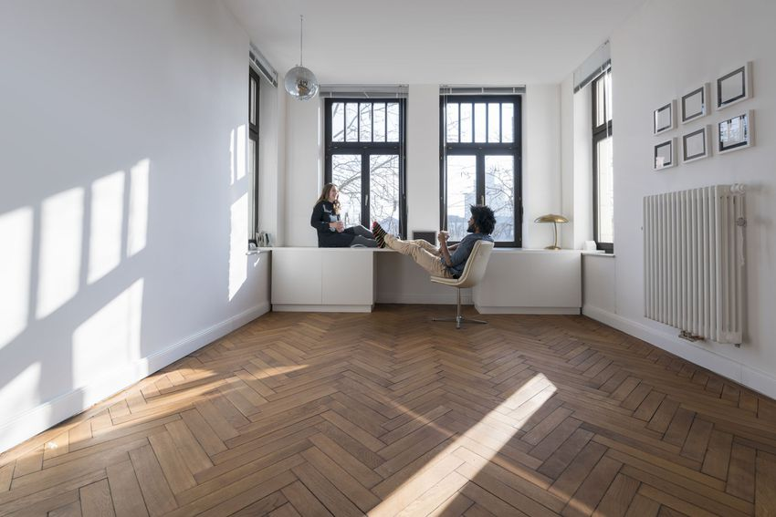 two people sitting and talking in a mostly empty room