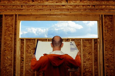 Back Of Man Reading Blueprints In Front A Wide And Narrow Opening Wall