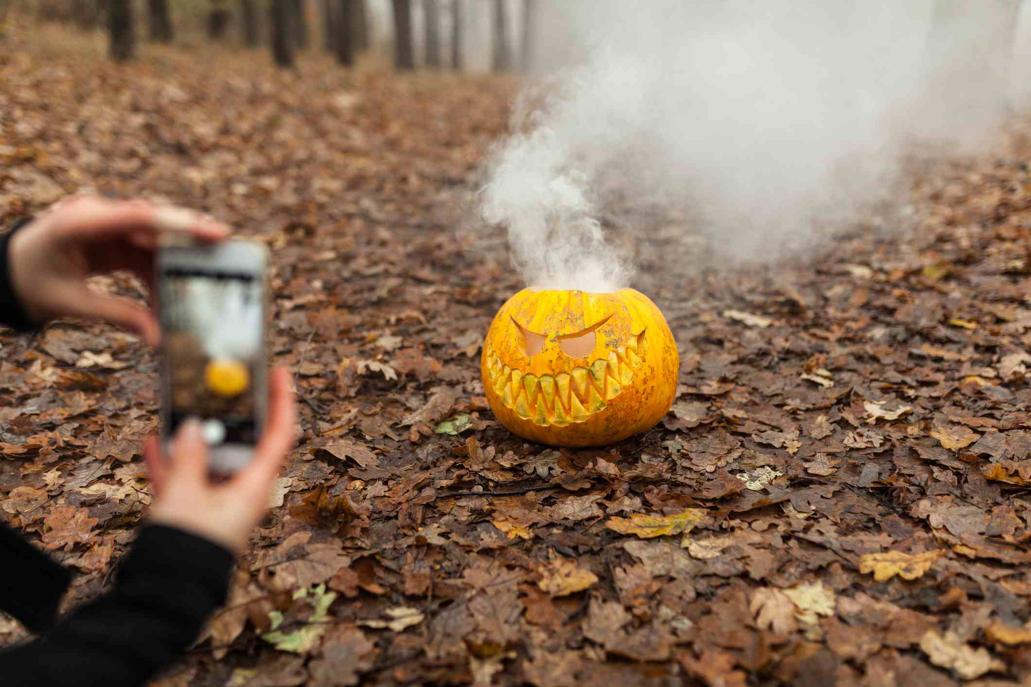 Person taking a photo of a jack o lantern with their smartphone