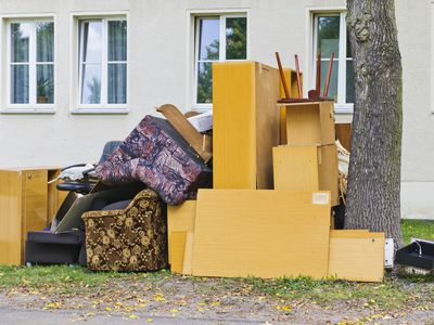 a pile of old furniture sitting outside a home