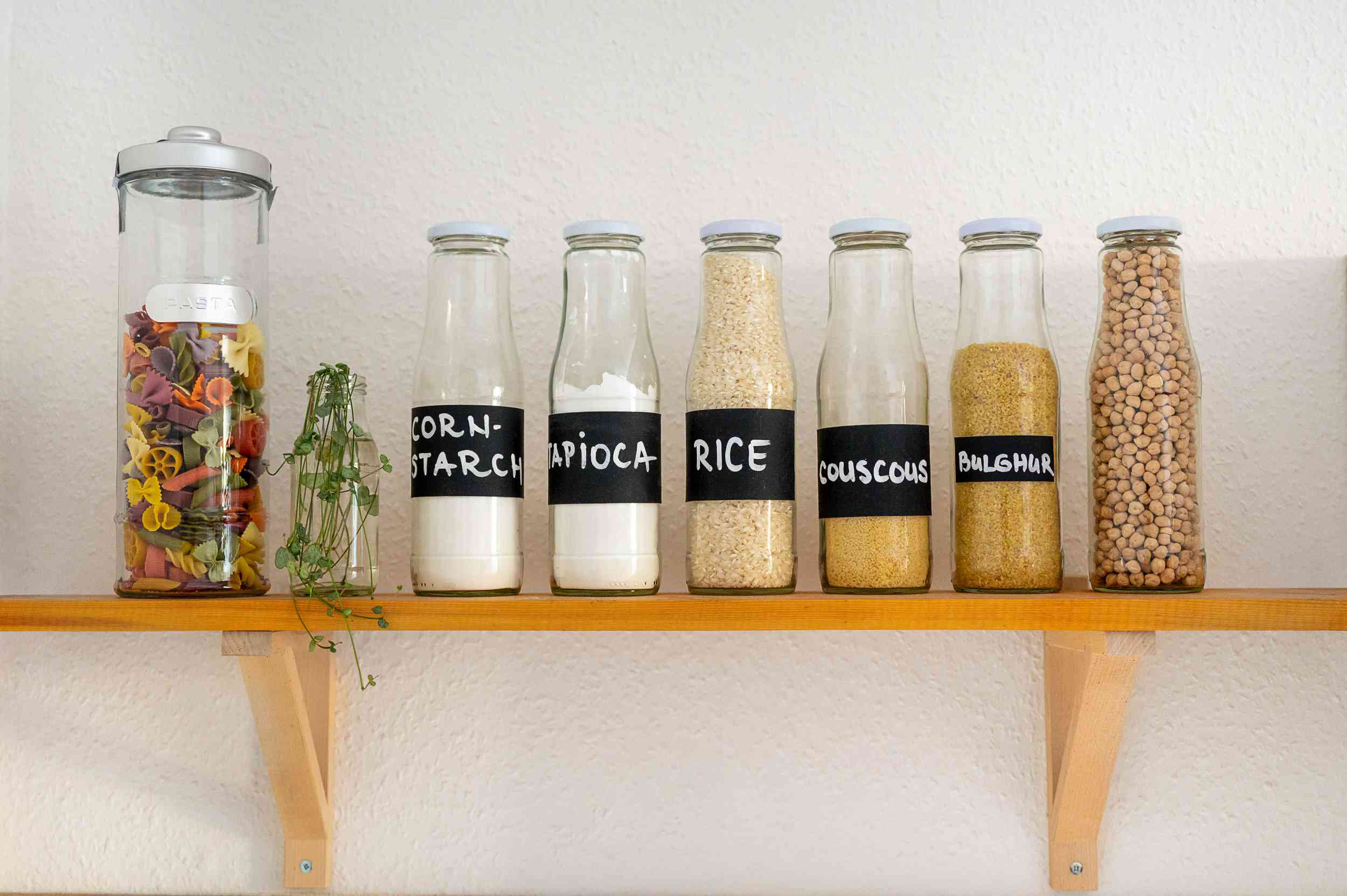 Tightly sealed glass containers labeled with different food items on kitchen shelf