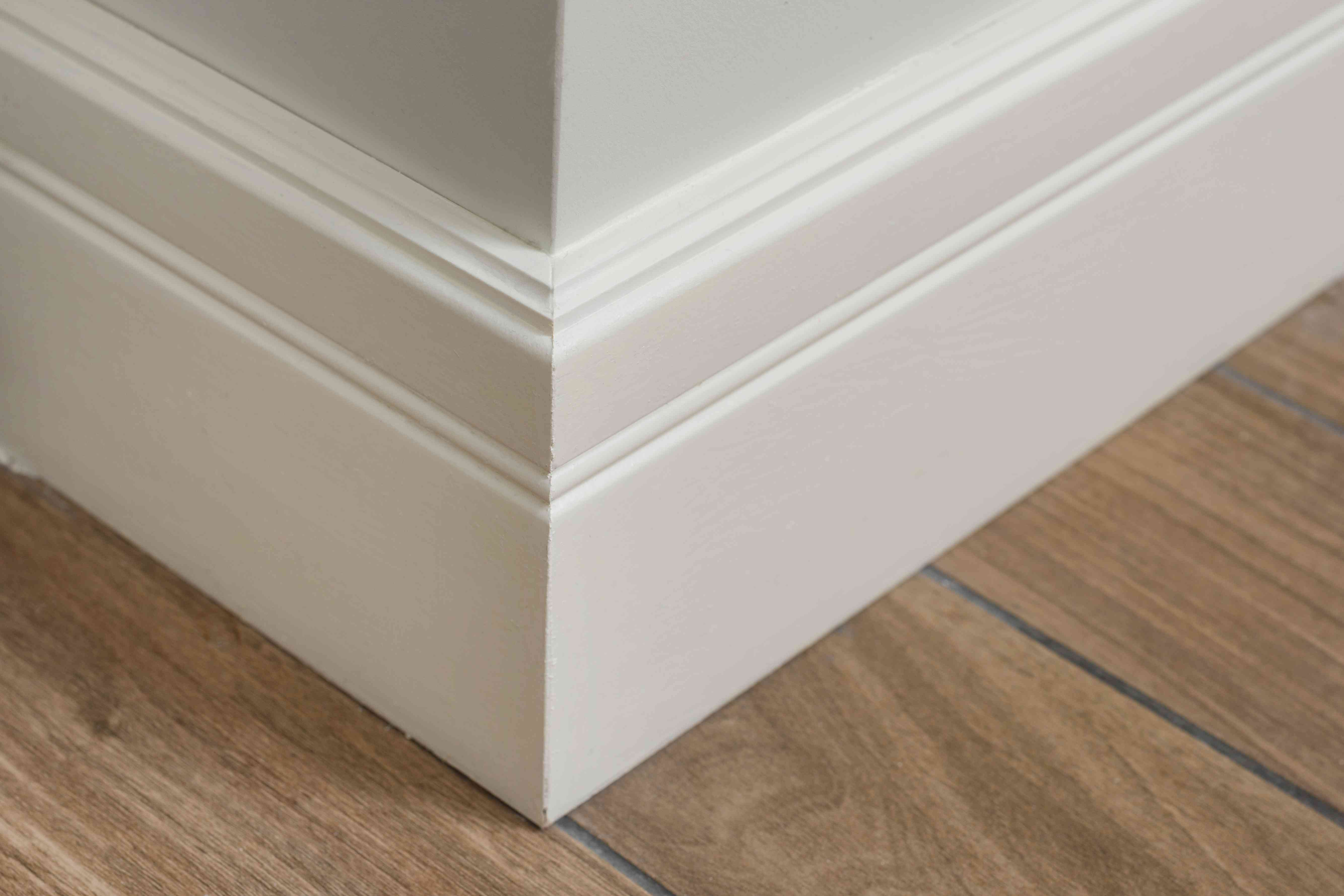 Molding in the interior, baseboard corner. Light matte wall with tiles immitating hardwood flooring