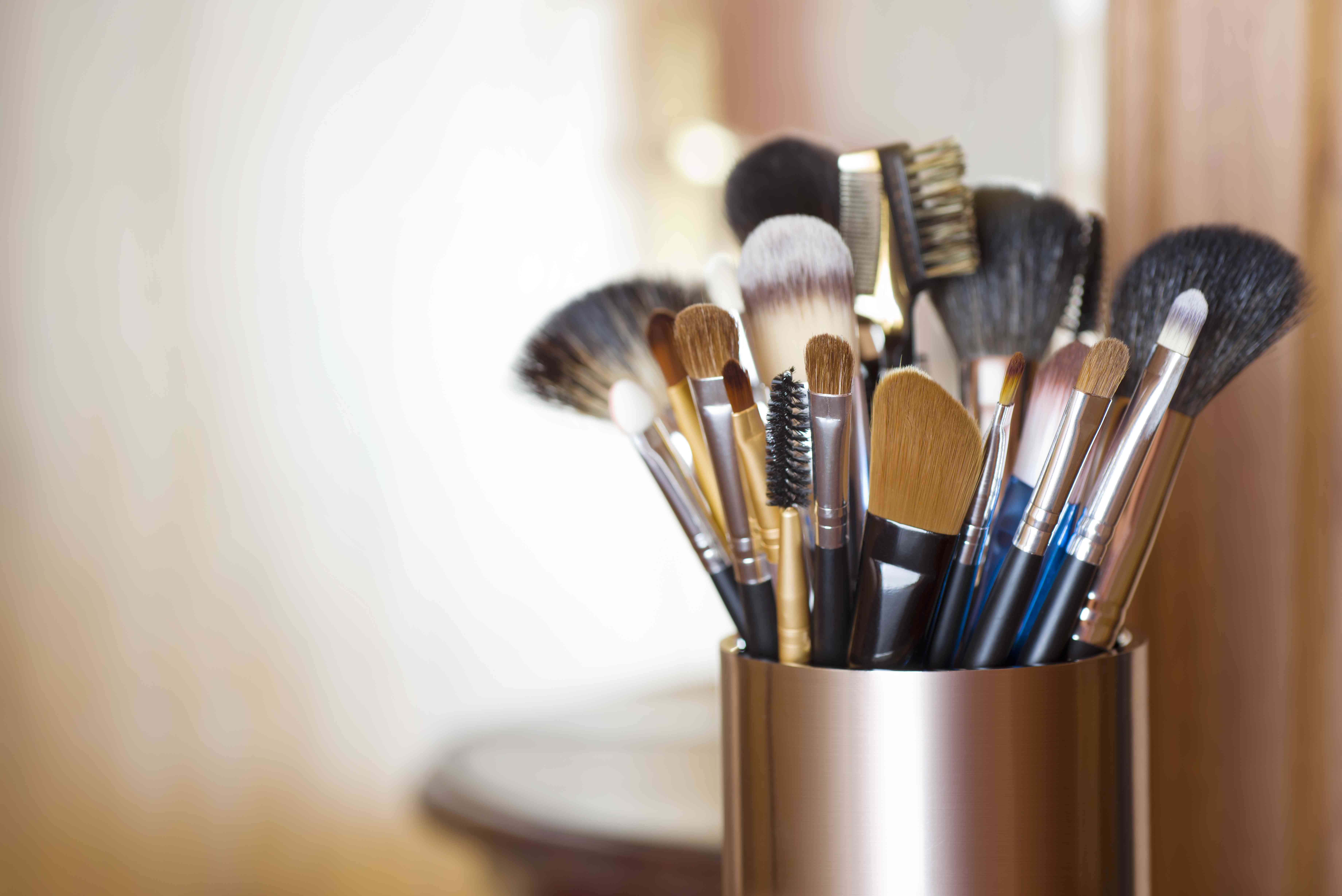 Makeup brushes in metal stand over blurred abstract room background