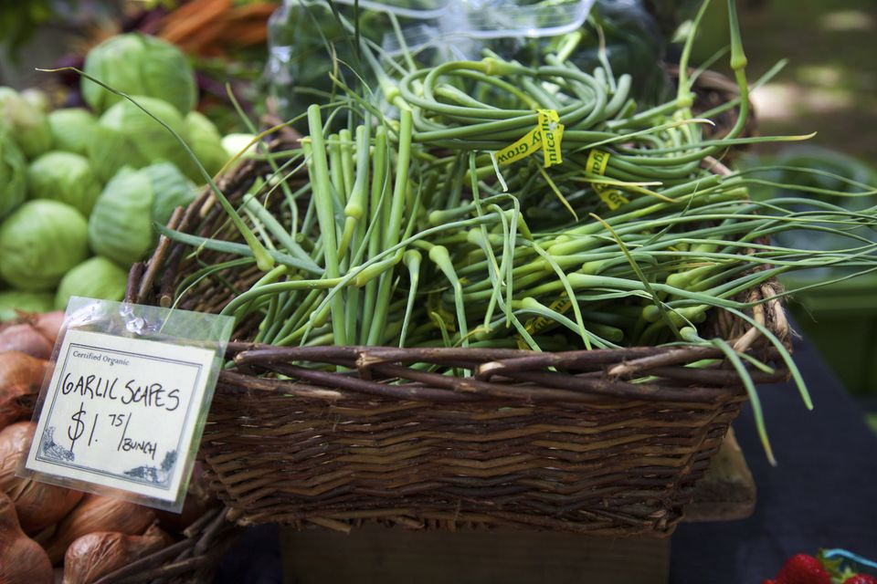A wicker basket full of garlic scapes