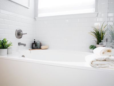 Refinished bathtub with white ceramic wall tiles decorated with plants and bath items