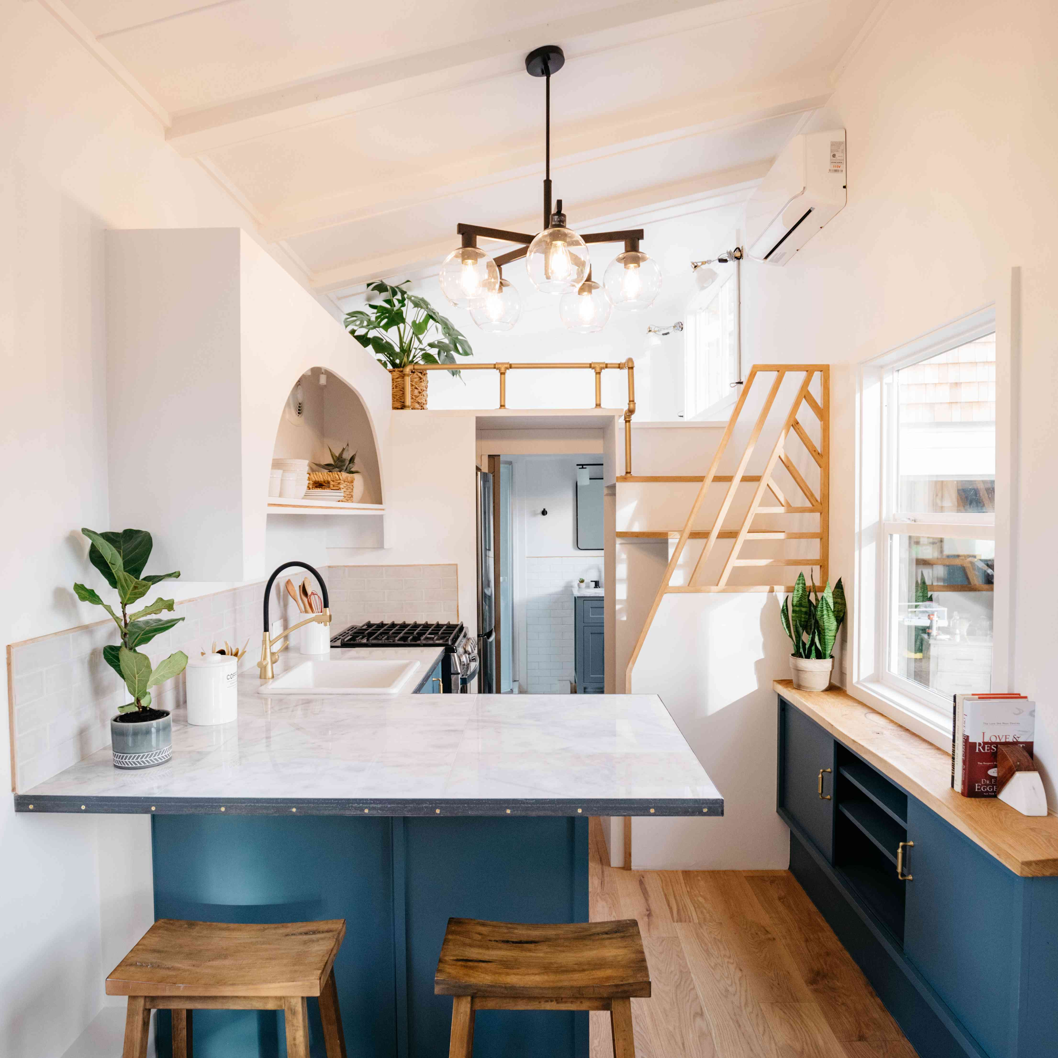 tiny home kitchen with blue cabinets and white marble with wood accents