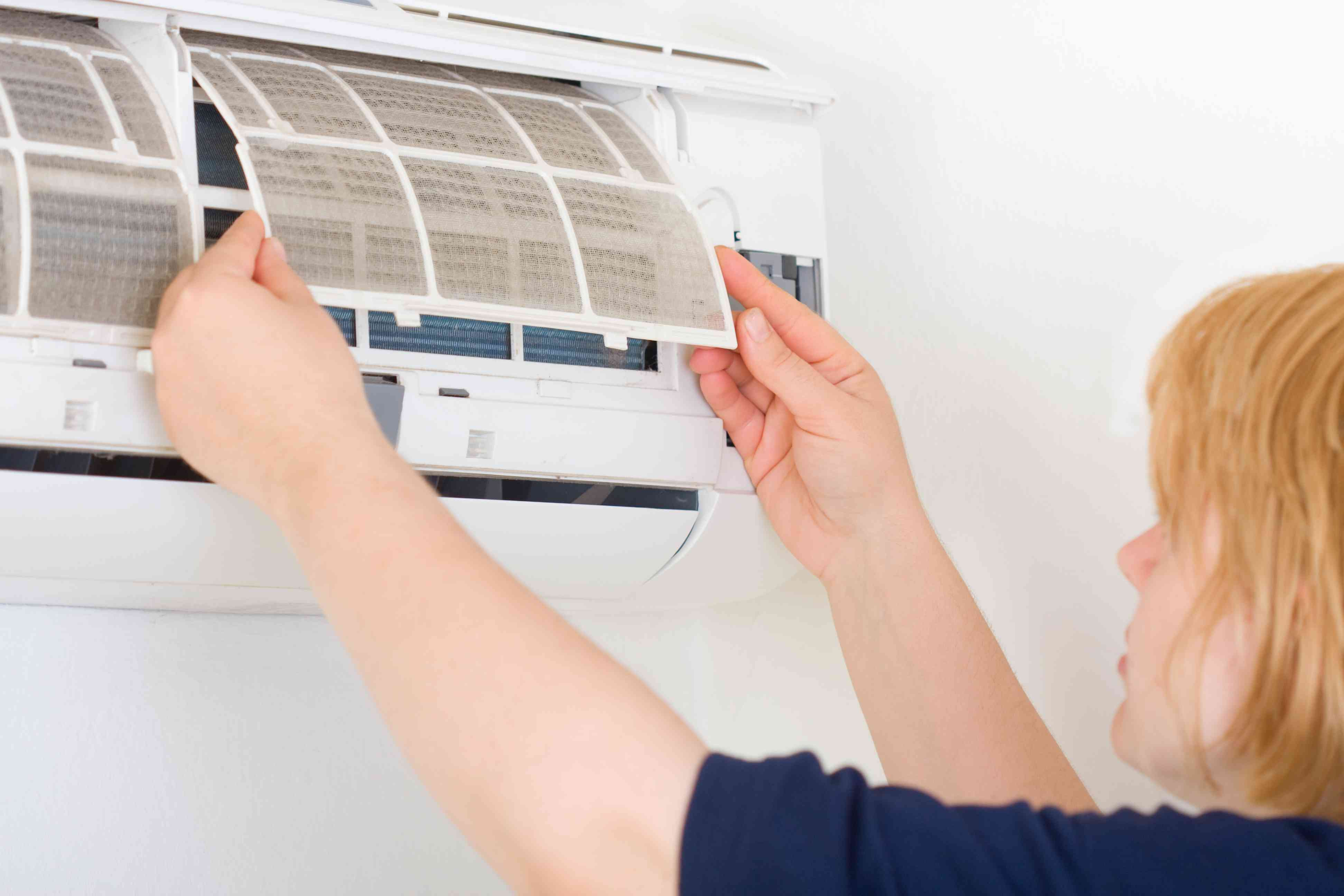 Woman Replacing an Air Filter in a Home