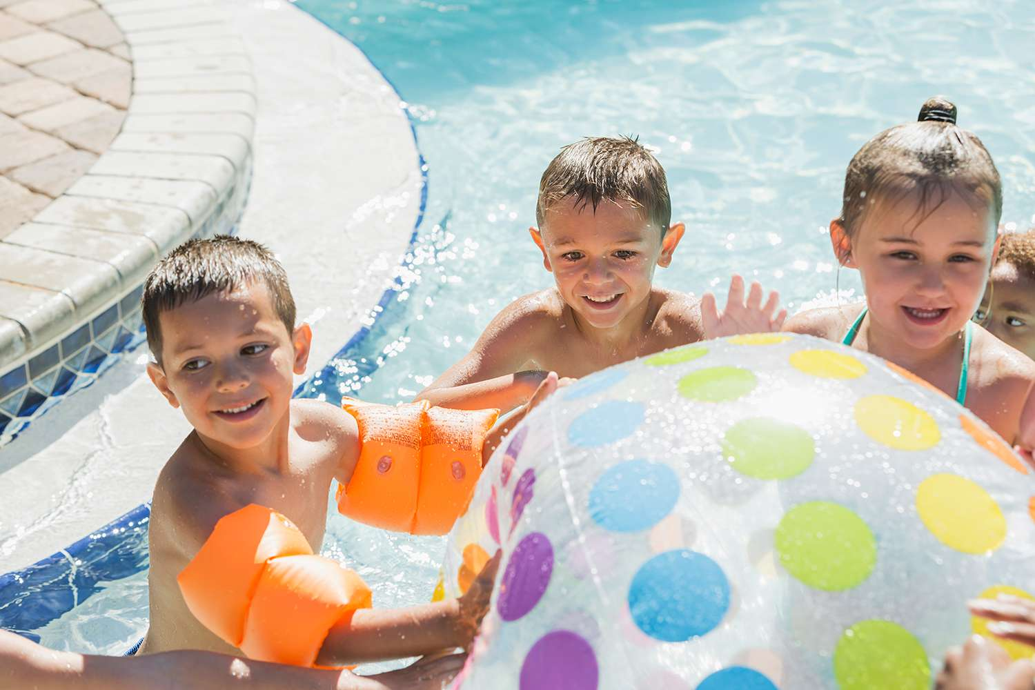 Multi-ethnic children with giant beach ball in pool