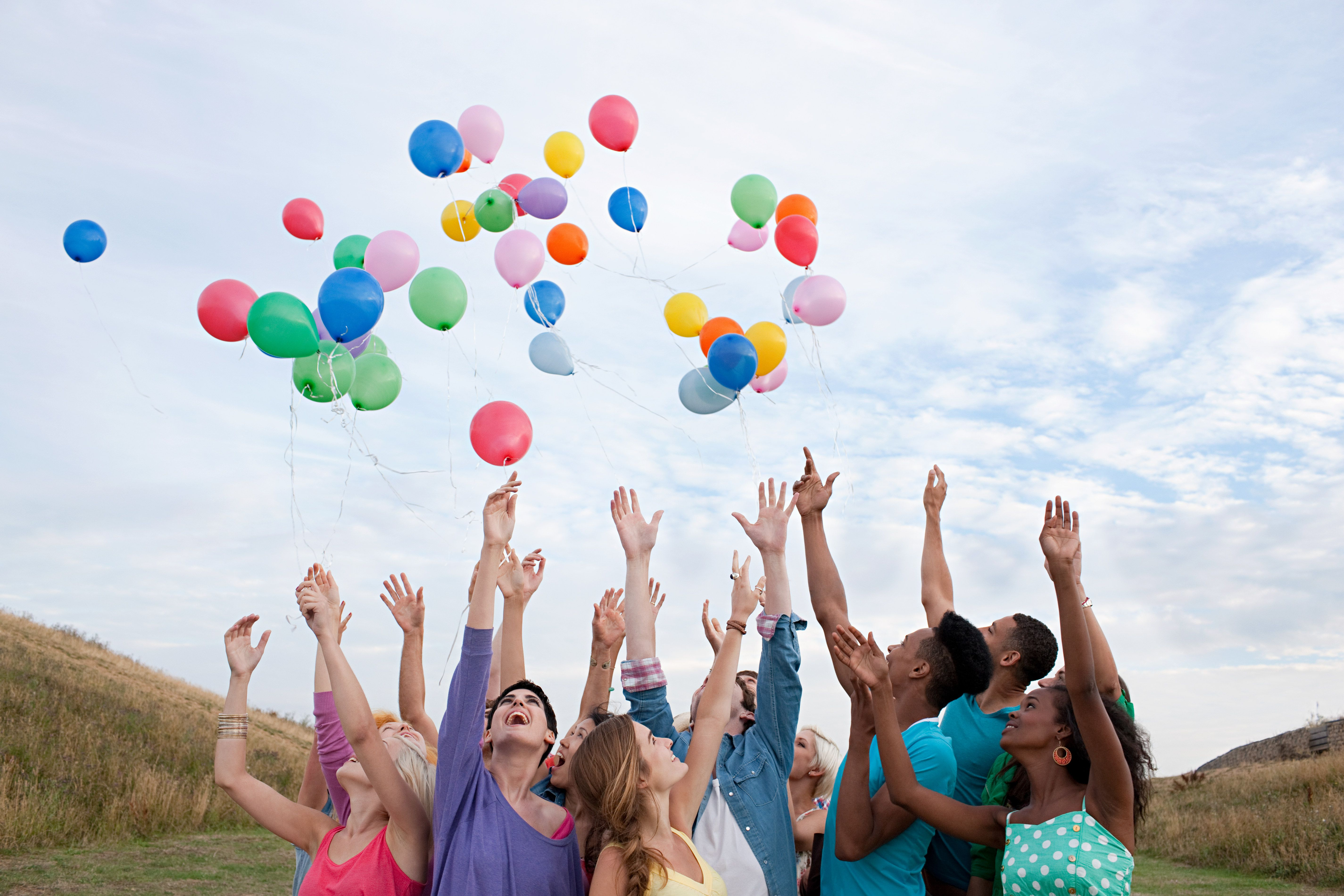 A group of young people releasing balloons
