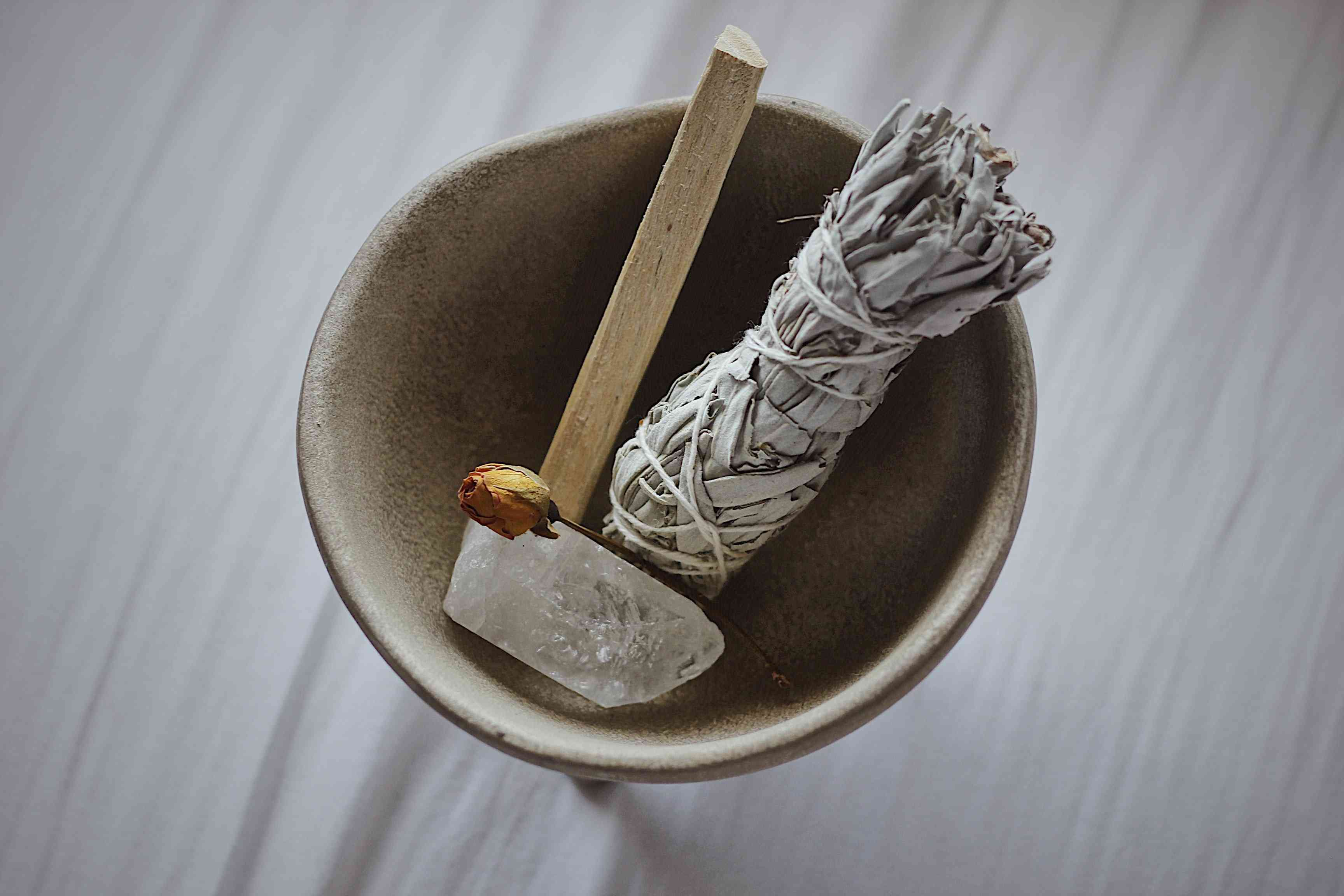 ceramic bowl with a crystal, palo santo, and sage