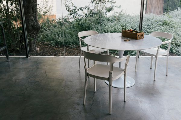 Modern Farmhouse Glass Kitchen With Three Plastic Chairs And Table On Concrete Flooring
