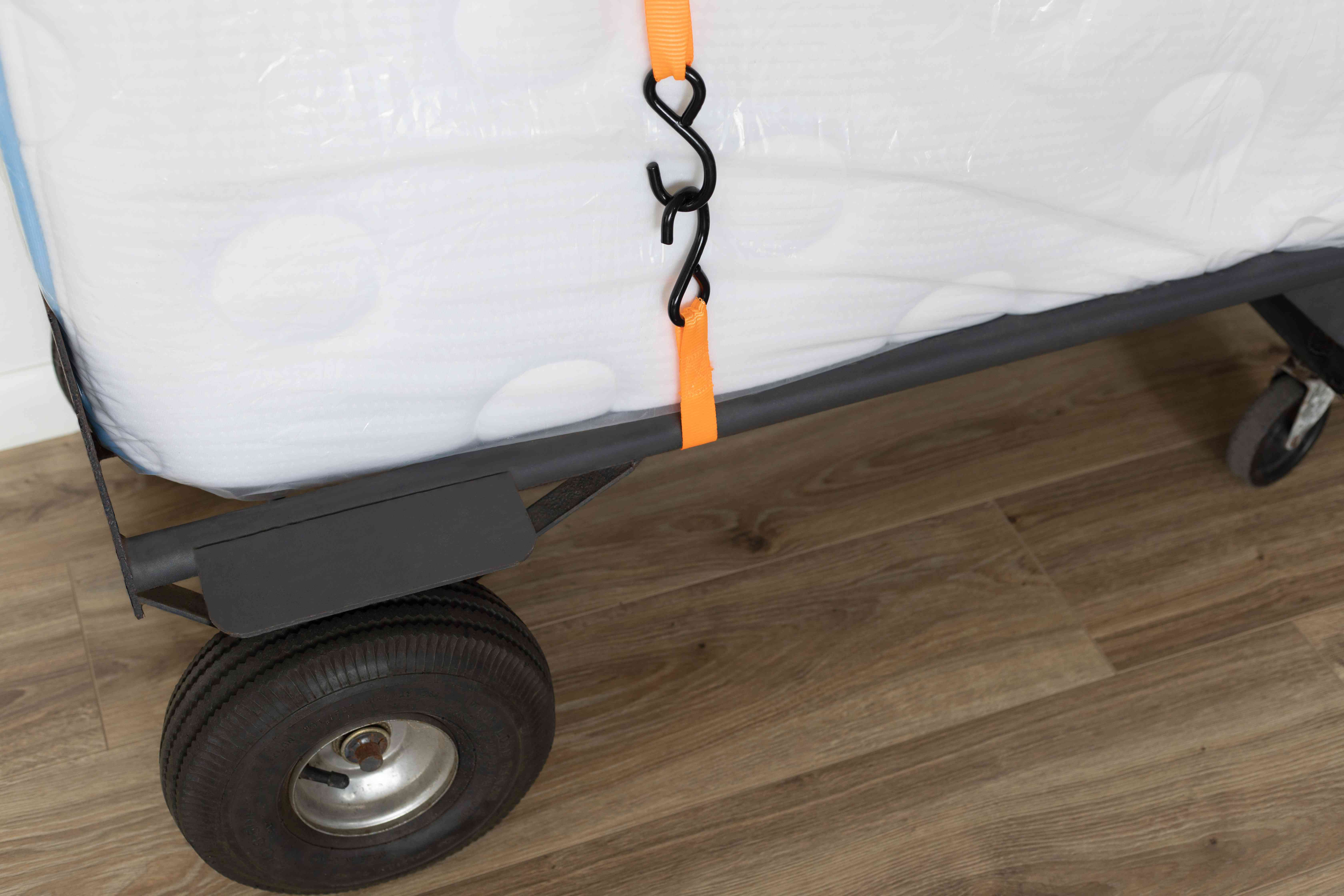 Mattress placed on furniture folly and secured with orange rachet straps for moving