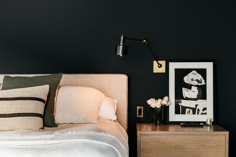Decorated bedroom with black walls with lighted bed-side lamp above nightstand