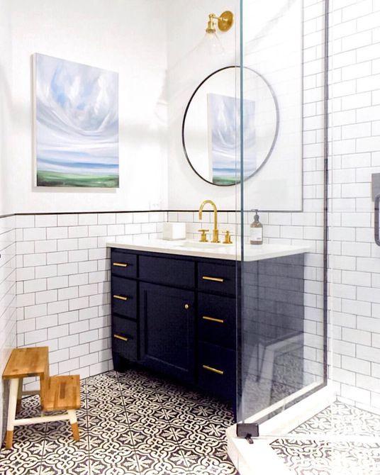 Baño con tocador azul marino y pisos de azulejos estampados