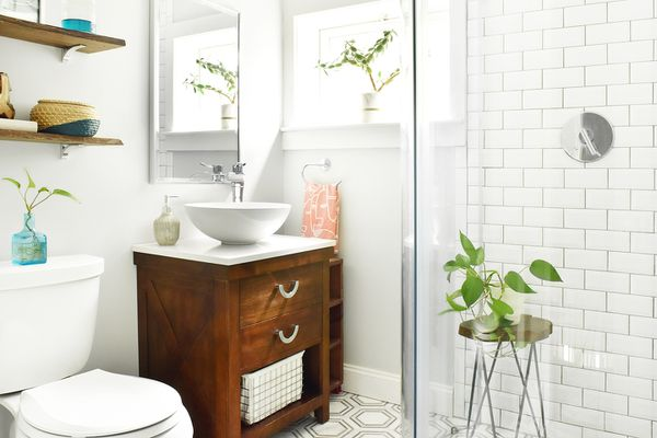 Small bathroom with glass shower wall and vessel sink with light decor and houseplants