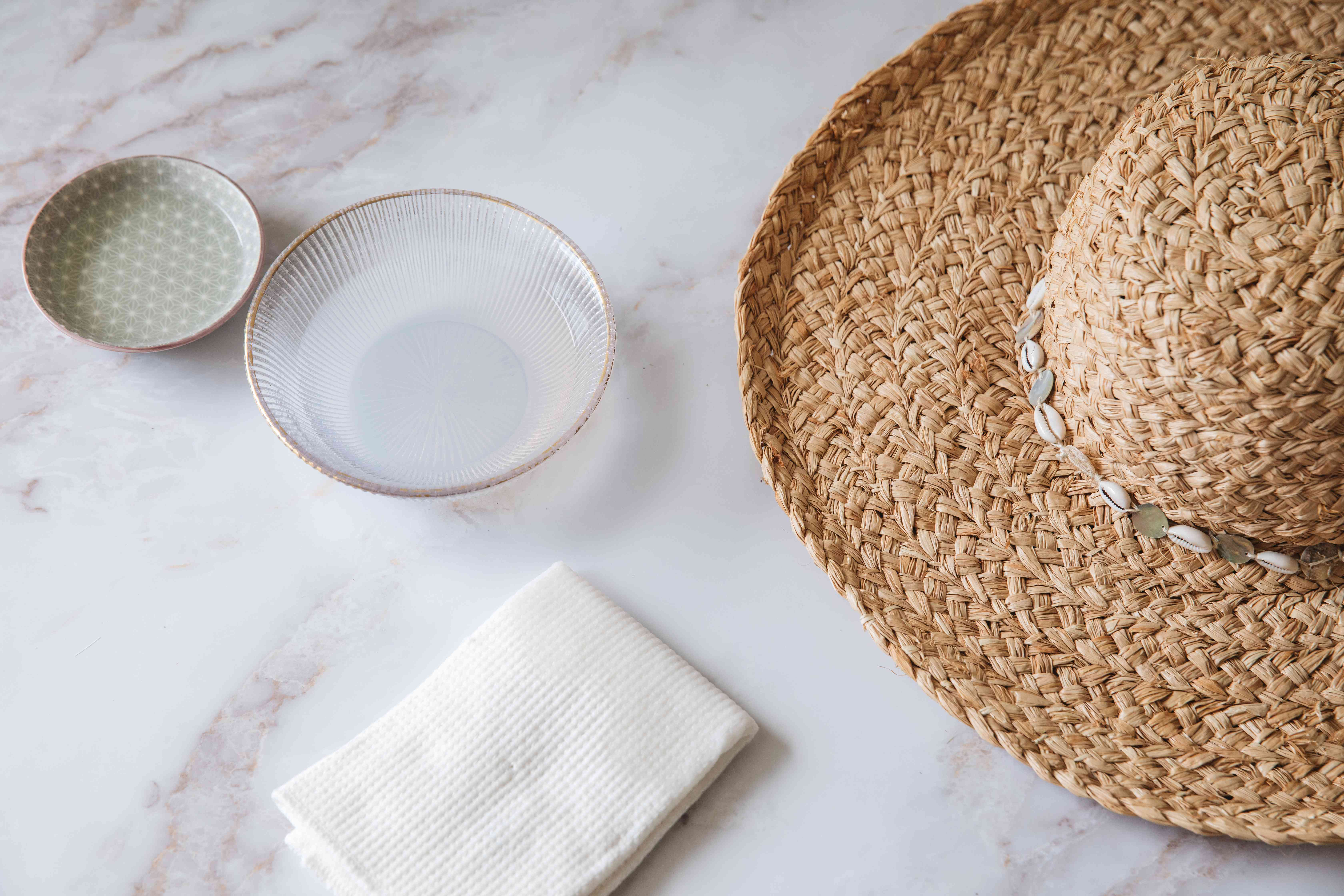 A straw hat with a white cloth and bowls of liquid
