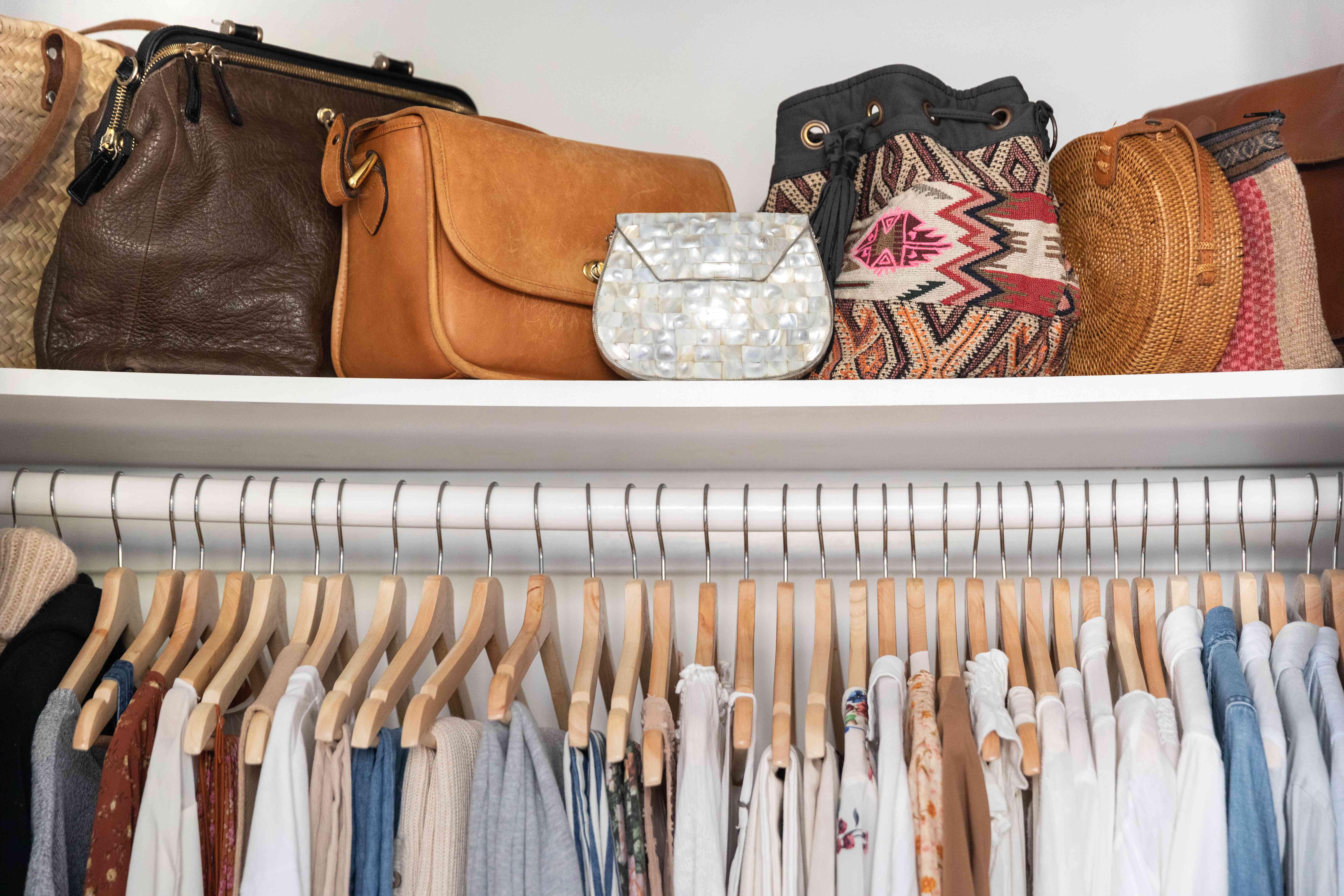 handbags stored on a shelf in a closet