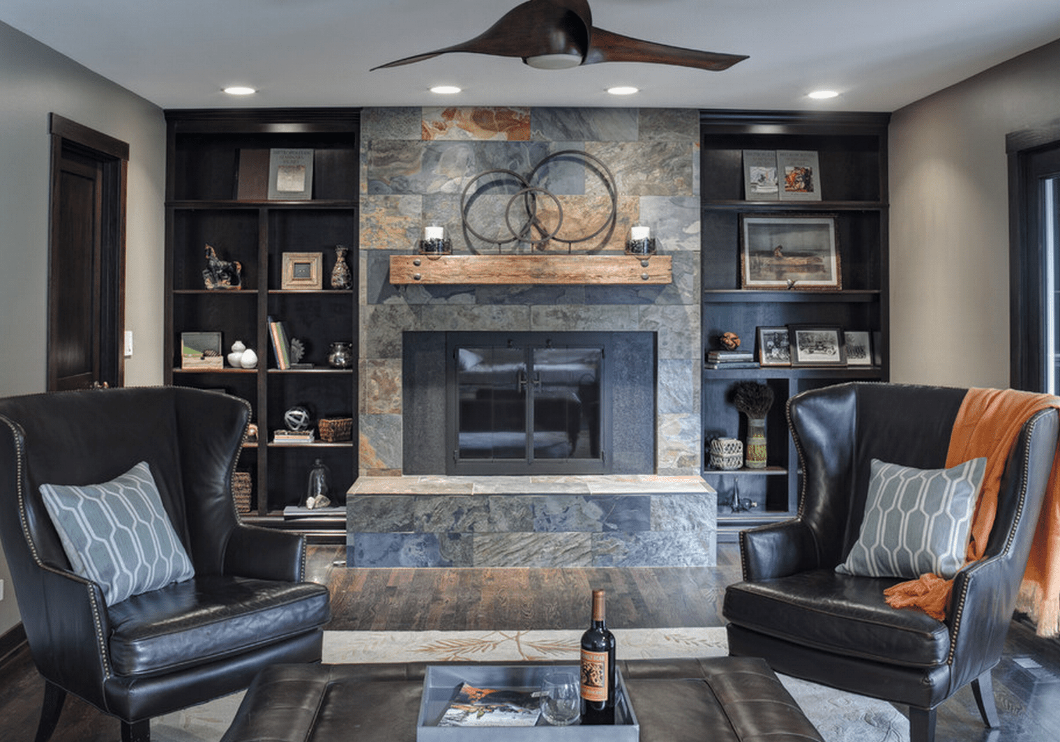 Living room with stone mantel, built ins and wing chairs