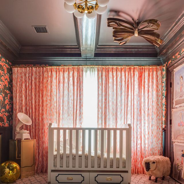 Gothic revival nursery room with black walls and dramatic floral wallpaper
