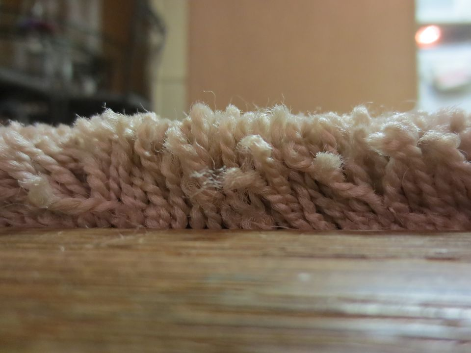 Close-up view of carpet fibers reaching up high