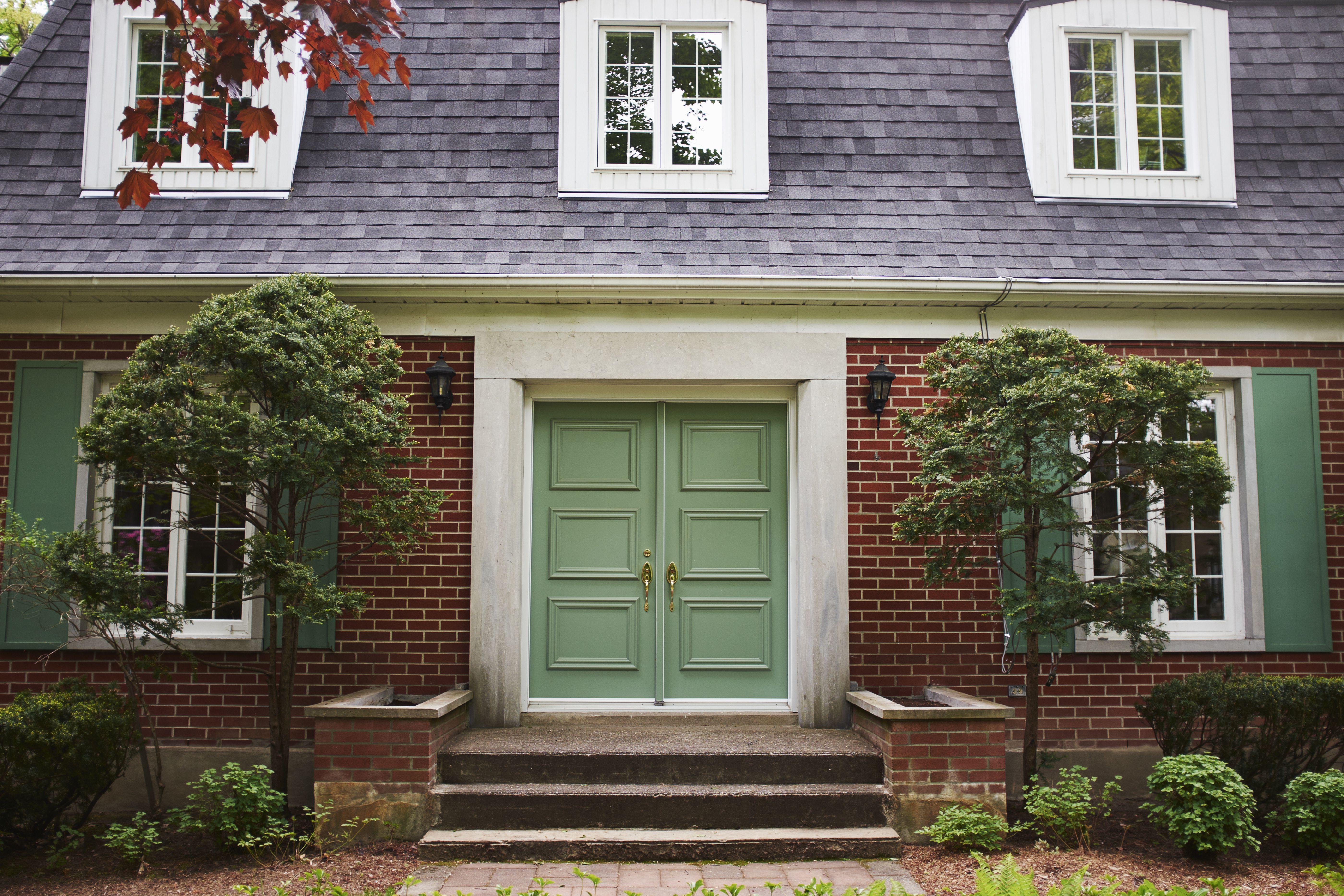 Casa de ladrillo con techo gris, buhardillas blancas y puertas y persianas verdes