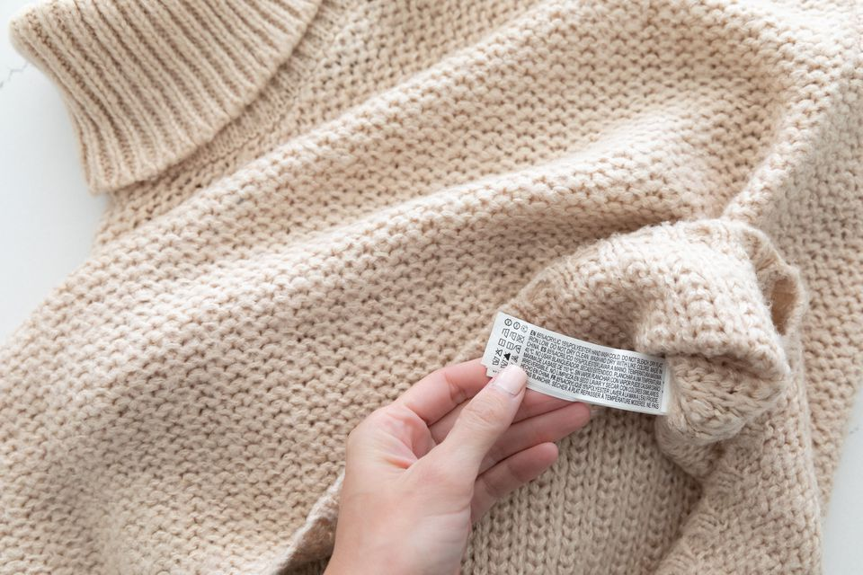 Acrylic knitted sweater with care labels being shown